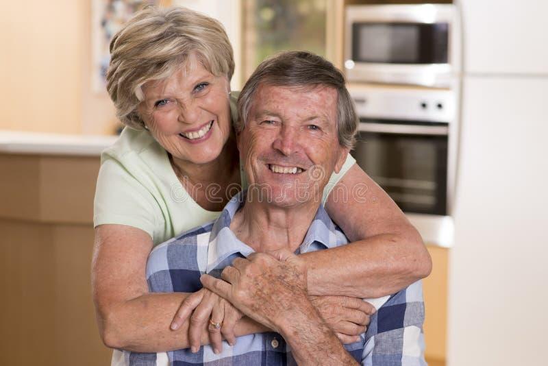 Starsza piękna wiek średni para wokoło 70 lat uśmiechający się szczęśliwego kuchennego przyglądającego cukierki w życie mężu wpól zdjęcie stock