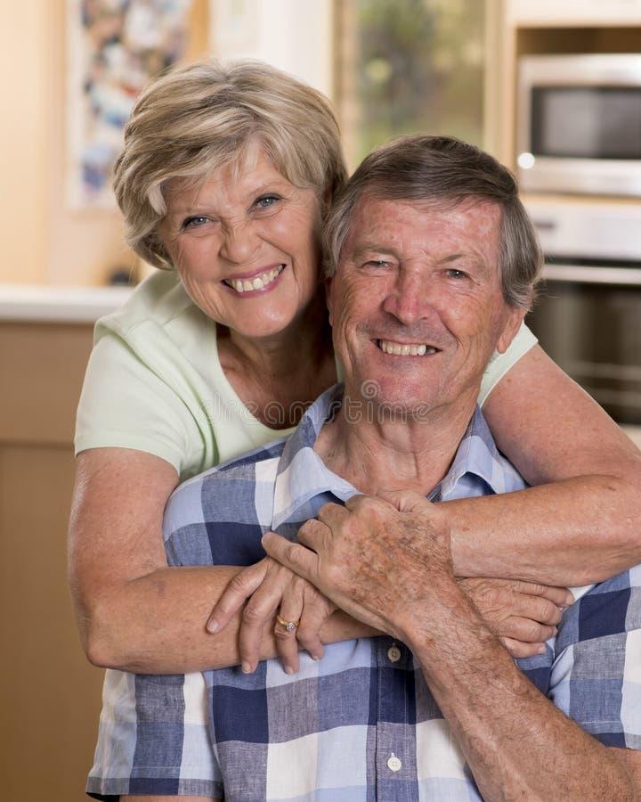 Starsza piękna wiek średni para wokoło 70 lat uśmiechający się szczęśliwego kuchennego przyglądającego cukierki w życie mężu wpól zdjęcia stock