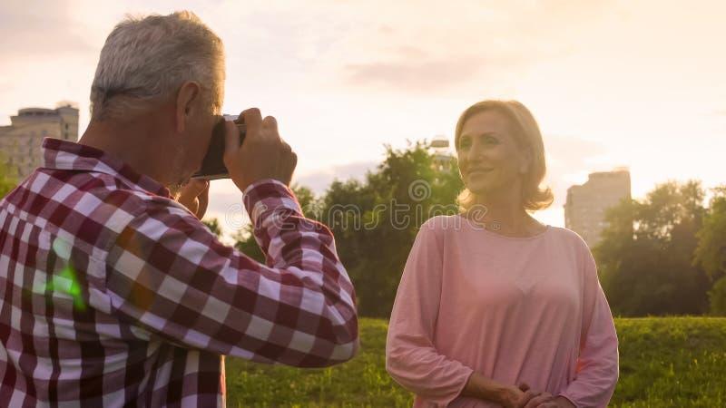 Starsza samiec fotografuje atrakcyjnej dojrzałej kobiety w parku, hobby i dacie, obraz stock