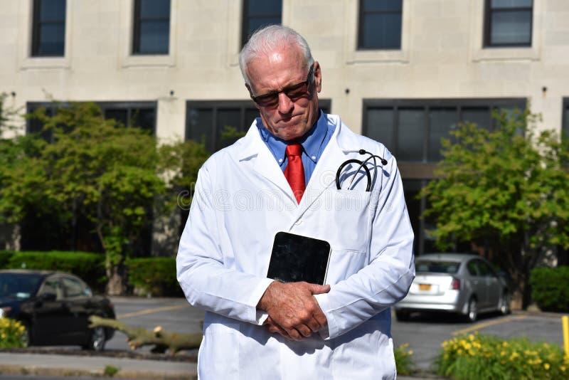 Starsza samiec lekarka, smucenie Jest ubranym Lab żakiet Z pastylką Przy szpitalem I fotografia royalty free
