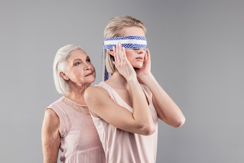 Starsza siwowłosa kobieta wiąże kawałek błękitna i biała tkanina obraz royalty free