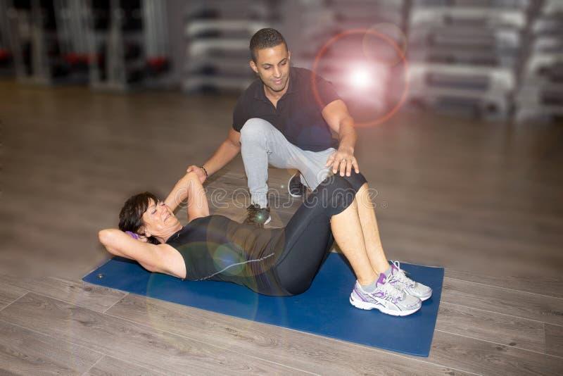 Starsza sport kobieta z sprawność fizyczna trenerem w gym centrum zdjęcie royalty free