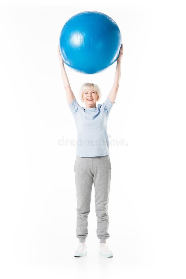 Starsza sportsmenka z rękami w górę mienie sprawności fizycznej piłki fotografia stock