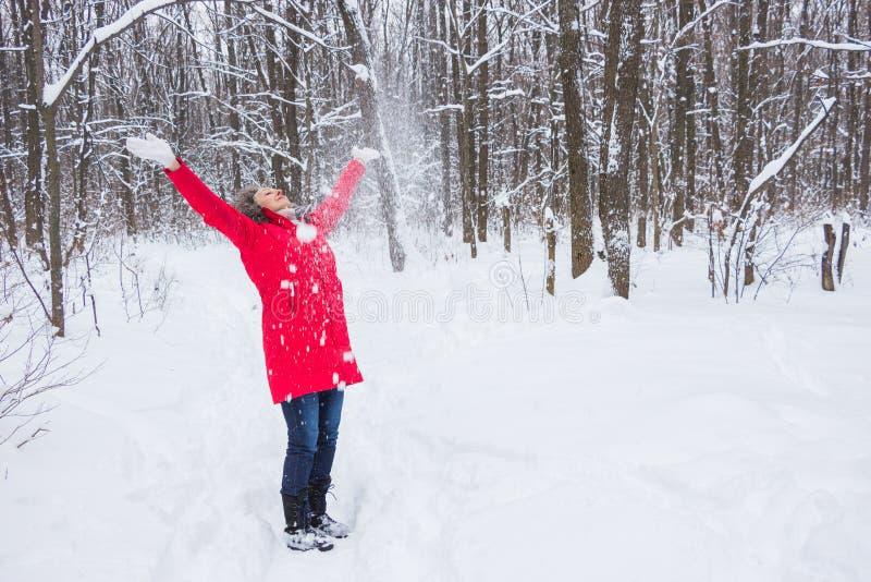 Starsza stara kobieta rzuca śnieg w drewnie w czerwonym żakiecie fotografia royalty free