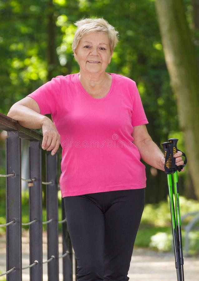 Starsza starsza kobieta ćwiczy północnego odprowadzenie, sporty style życia w starości obraz royalty free