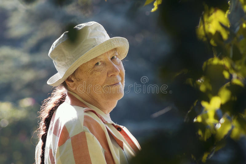 Starsza szczęśliwa kobieta ono uśmiecha się w ogródzie lub paek zdjęcia royalty free