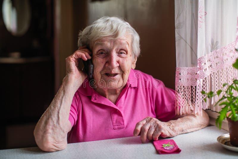 Starsza szczęśliwa starsza kobieta opowiada na telefonie komórkowym zdjęcia stock