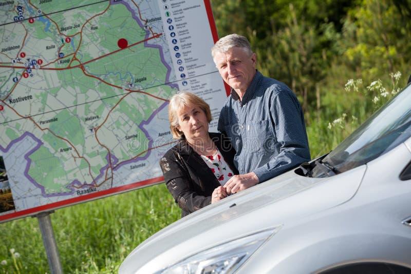 Starsza szczęśliwa para podróżuje samochodem, stoi wpólnie blisko drogowej mapy stojaka zdjęcia stock