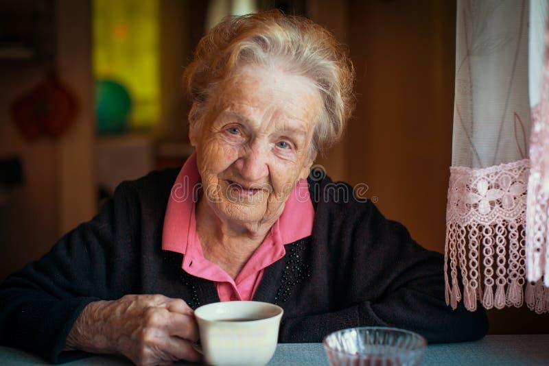 Starsza szczęśliwa przechodzić na emeryturę kobieta pije herbaty w jego domu fotografia stock