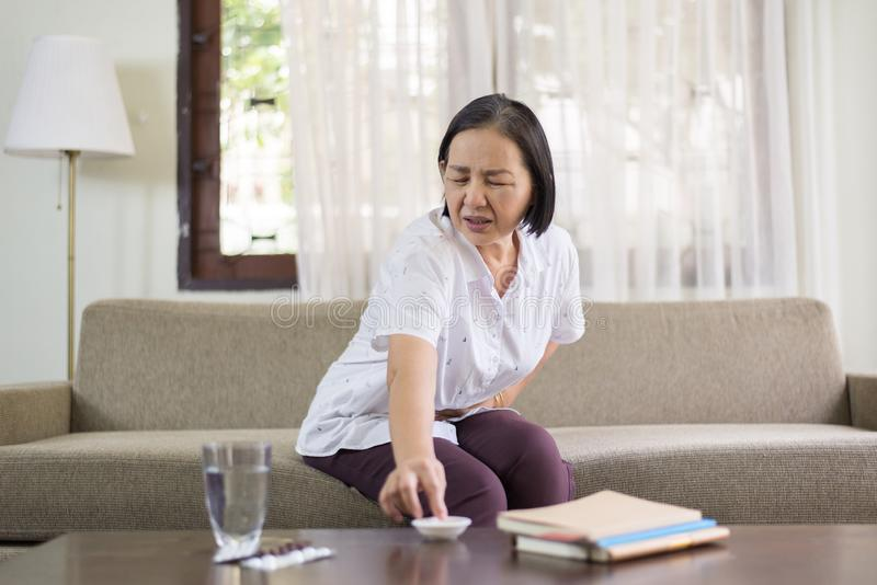 Starsze azjatykcie kobiety ma bolesnego w domu, Starszy żeński cierpienie od brzusznego bólu zdjęcia stock