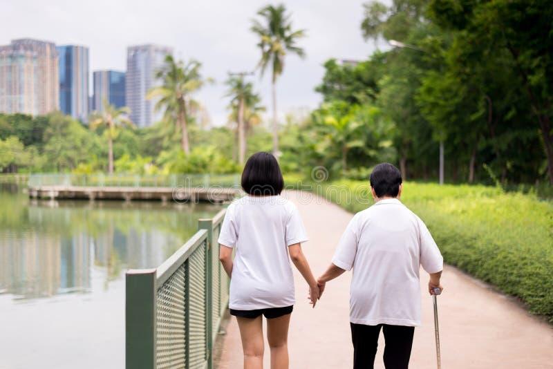 Starsze azjatykcie kobiety stoi robić badaniu lekarskiemu z kijem przy plenerowym w ranku i chodzi, dozorca biorą opiekę i poparc obrazy stock