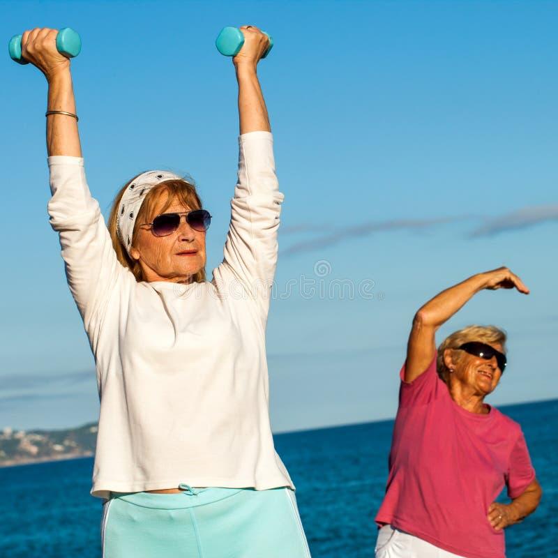 Starsze damy robi sprawności fizycznej ćwiczą na plaży. fotografia stock