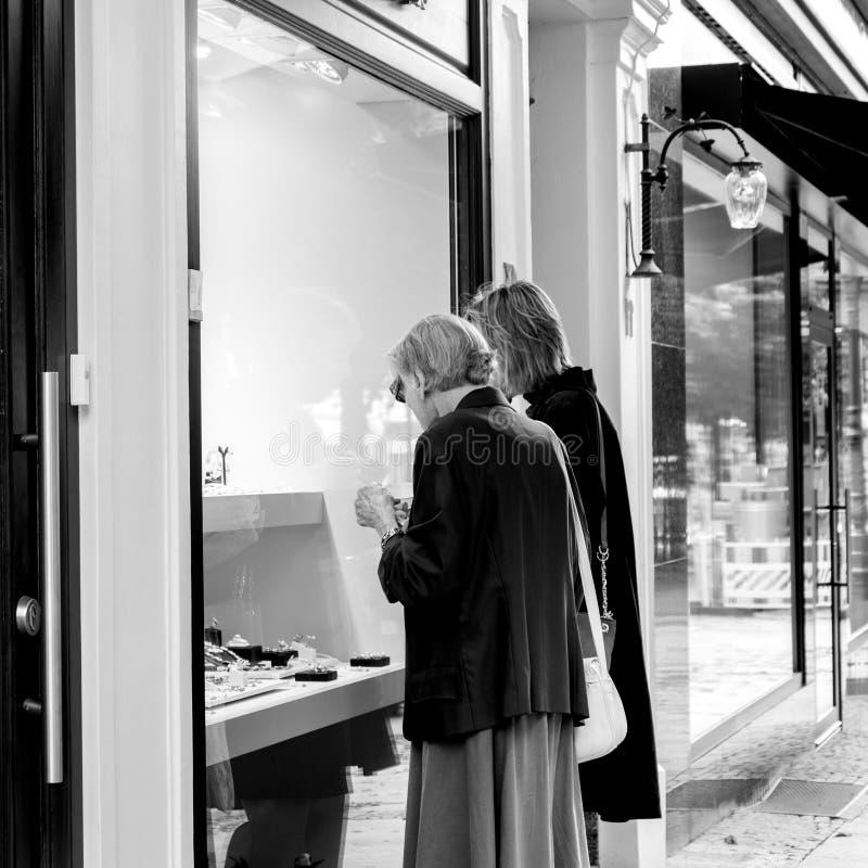 Starsze i dorosłe kobiety jedzie w gablocie wystawowej na luksusowej ulicie obrazy stock