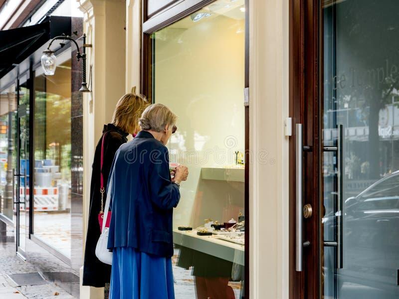 Starsze i dorosłe kobiety jedzie w gablocie wystawowej na luksusowej ulicie zdjęcie stock