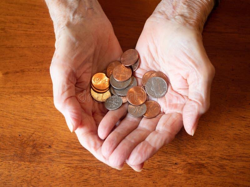 Starsze kobiet ręki Trzyma wielokrotność monety zdjęcia royalty free