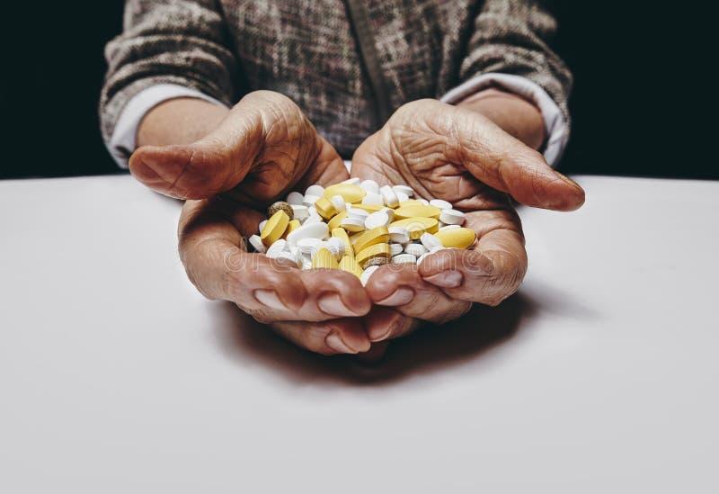 Starsze kobiet ręki z pigułkami obrazy royalty free