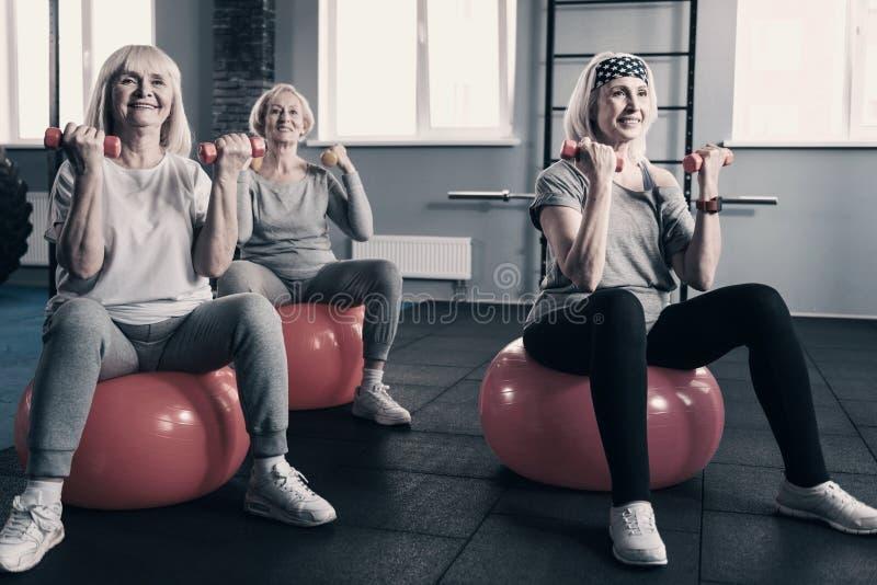 Starsze kobiety ćwiczy z dumbbells na sprawności fizycznych piłkach zdjęcie stock