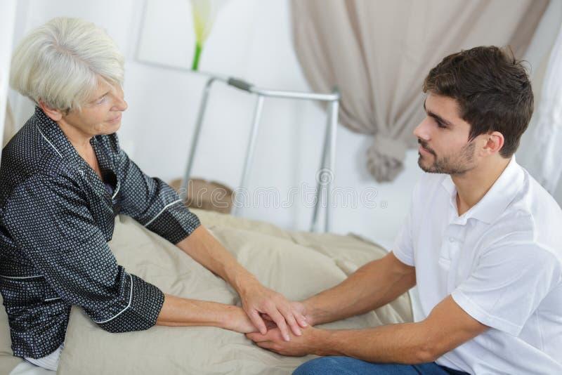 Starsze kobiety i potomstwo opiekunu mienia ręki obrazy stock