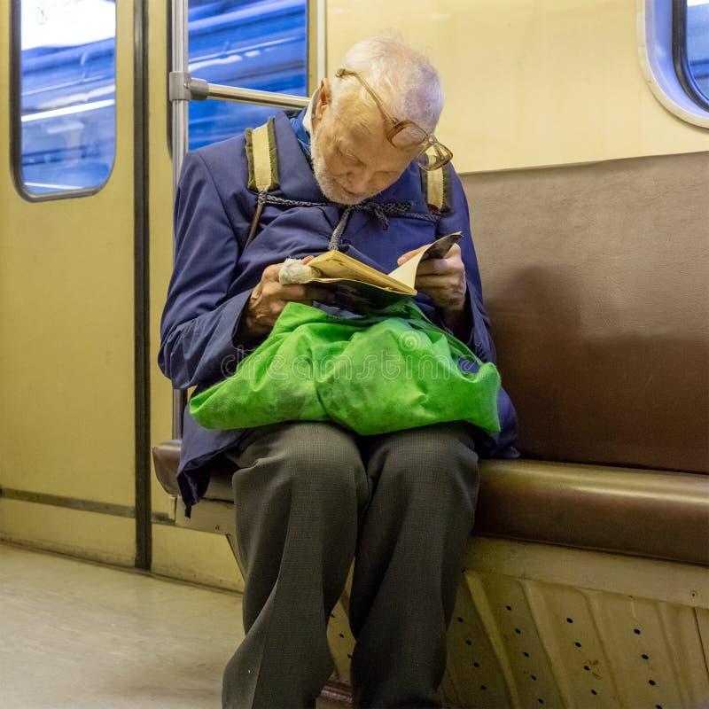 Starsze osoby, bieda, osamotniony mężczyzna entuzjastycznie czyta szargającą książkę w łamanych szkłach zdjęcia stock