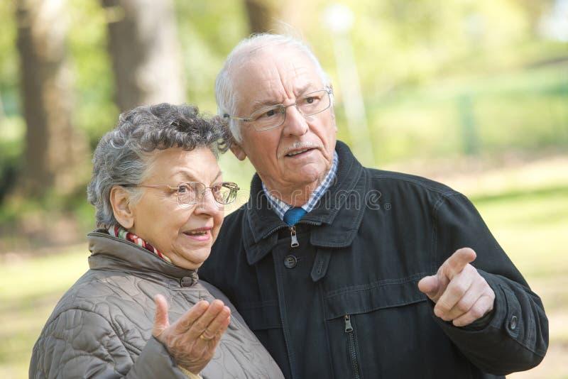 Starsze osoby dobierają się outdoors wskazywać zdjęcia stock