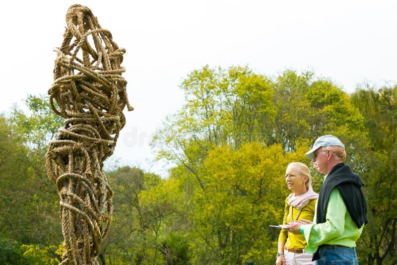 Starsze osoby dobierają się podziwiać rzeźbę przy wina wydarzeniem zdjęcie royalty free