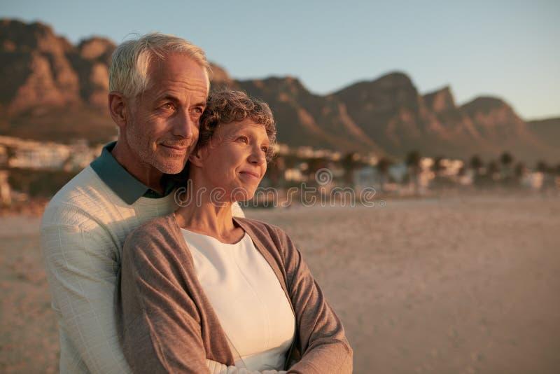 Starsze osoby dobierają się pozycję i obejmowanie na plaży wpólnie zdjęcie royalty free