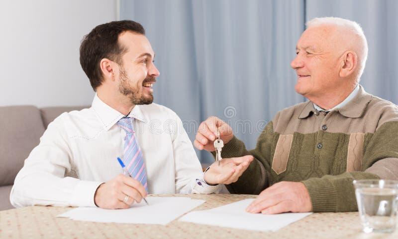 Starsze osoby i agentów czynszowi mieszkania obsługują obraz stock