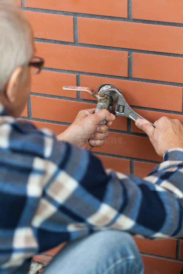 Starsze osoby obsługują śrubującego klucza klepnięcie obraz stock