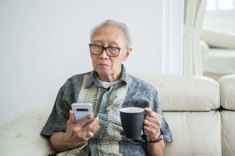 Starsze osoby obsługują cieszą się wolnego czas herbatą i telefonem obrazy stock