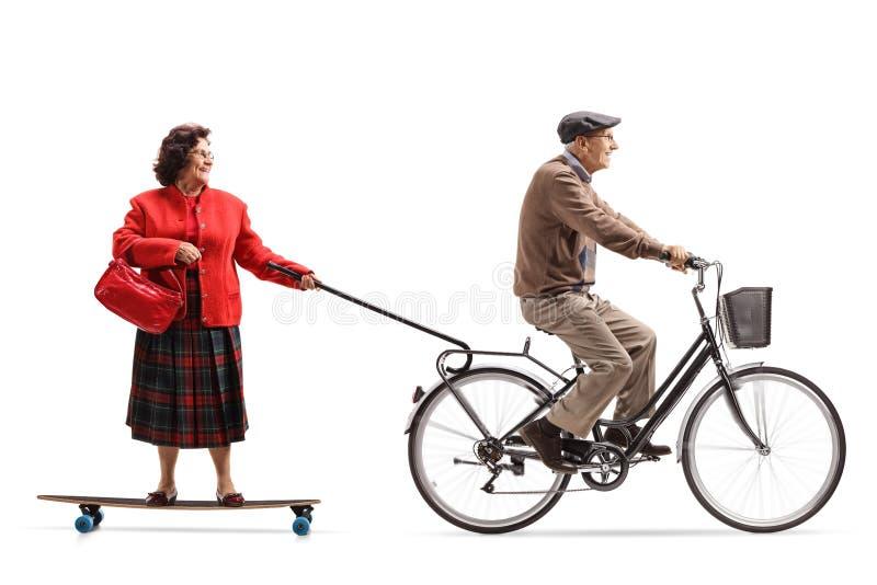 Starsze osoby obsługują na rowerowym ciągnięciu starszej kobiety na longboard zdjęcie stock