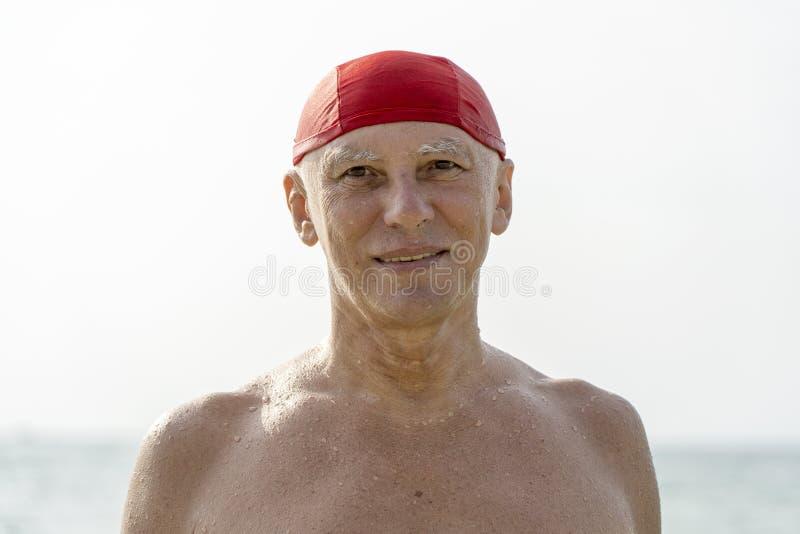 Starsze osoby obs?uguj? w czerwonym p?ywackim kapeluszu na pla?y blisko wody morskiej fotografia royalty free