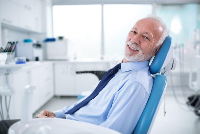 Starsze osoby obsługują w dentysty ` s krześle czeka treatmen bez strachu zdjęcie royalty free