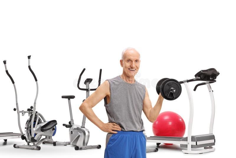 Starsze osoby obsługują z dumbbell przed ćwiczenie maszynami zdjęcia stock