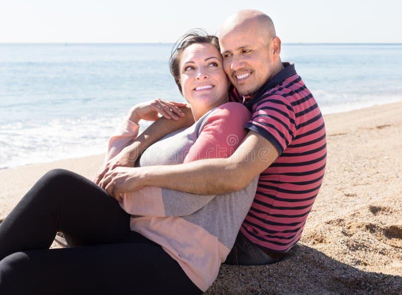 Starsze osoby obsługują z kobiety obsiadaniem na piasku na plaży fotografia royalty free
