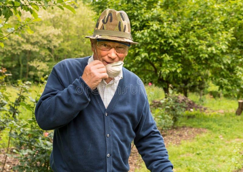 Starsze osoby obsługują z zbawczymi szkłami, maska i kapelusz pracuje w ogródzie obraz stock
