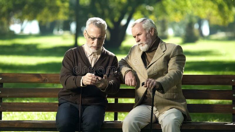 Starsze osoby obs?uguj? pyta? przyjaciela dla pomocy z m?drze telefonem, nowe nowo?ytne technologie zdjęcie stock