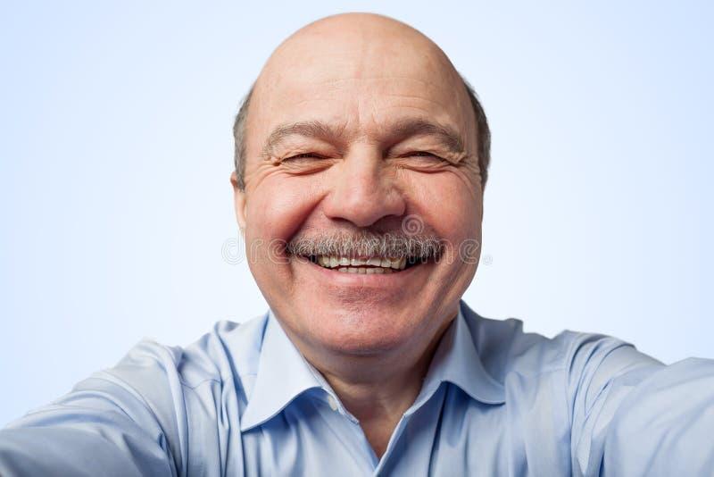 Starsze osoby trzyma smartphone obsługują z wąsy i robią selfie, ono uśmiecha się szeroko zdjęcia royalty free