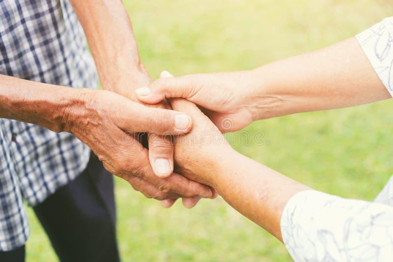 Starsze pary trzymają ręki, pojęcie biorą opiekę wpólnie zdjęcie stock