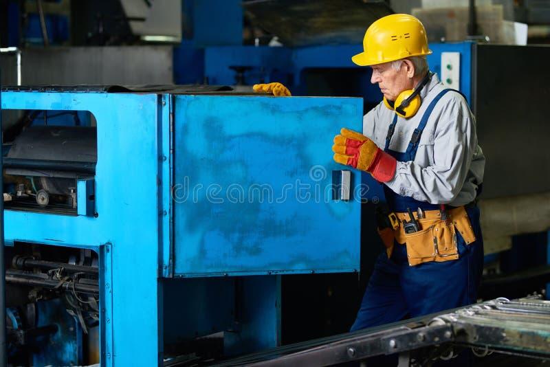 Starsze pracownika fabrycznego naprawiania maszyny obraz royalty free