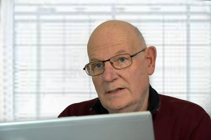 Starsze szef niezobowiązująco ubierać pracy w jego biurze fotografia stock