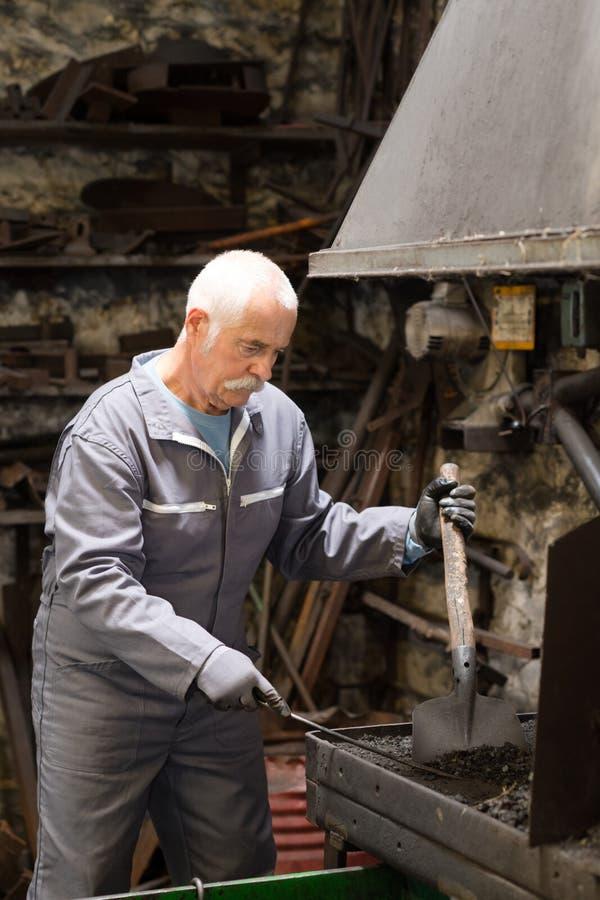 Starszego blacksmith skucia stopiony metal fotografia stock