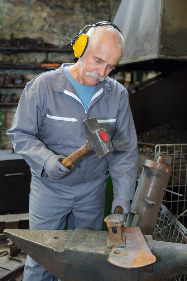 Starszego blacksmith skucia stopiony metal na kowadle obraz royalty free