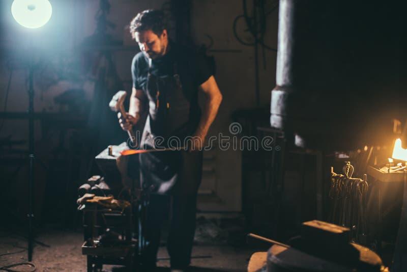 Starszego blacksmith skucia stopiony metal na kowadle w smithy fotografia stock
