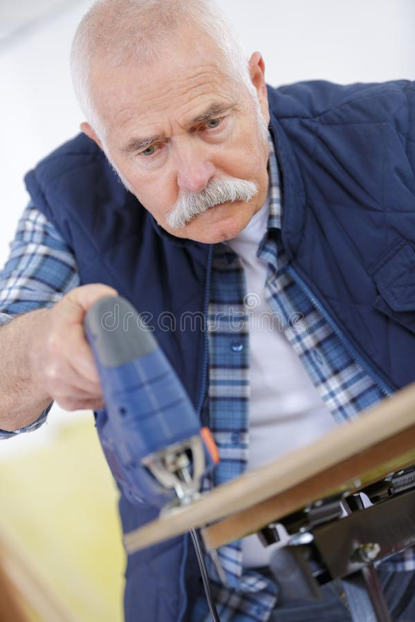 Starszego cieśli tnący drewno z bandsaw w warsztacie zdjęcia stock