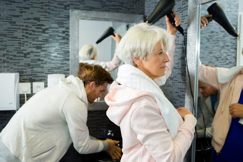 Starszego kobieta ciosu suszarniczy włosy po gym zdjęcie royalty free