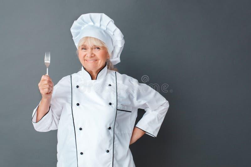 Starszego kobieta szefa kuchni pracowniana pozycja odizolowywająca na szarość z rozwidlenie dumną przyglądającą kamerą rozochocon zdjęcie royalty free