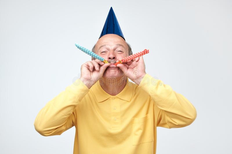 Starszego mężczyzny dmuchania przyjęcia róg ma z podnieceniem spojrzenie podczas gdy świętujący urodziny obrazy stock