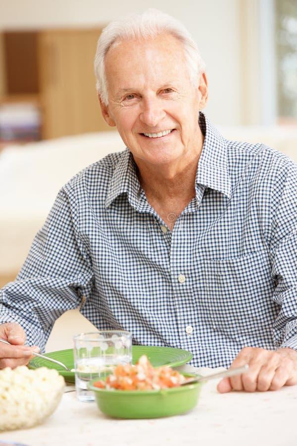 Starszego mężczyzna łasowania posiłek obraz royalty free