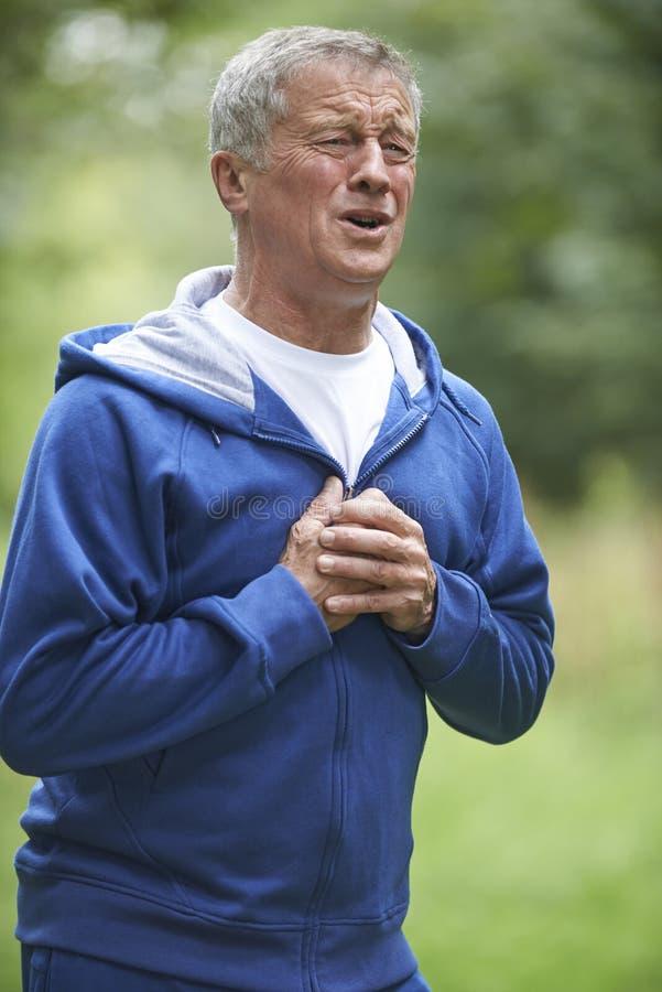 Starszego mężczyzna cierpienia atak serca Podczas gdy Jogging zdjęcia stock