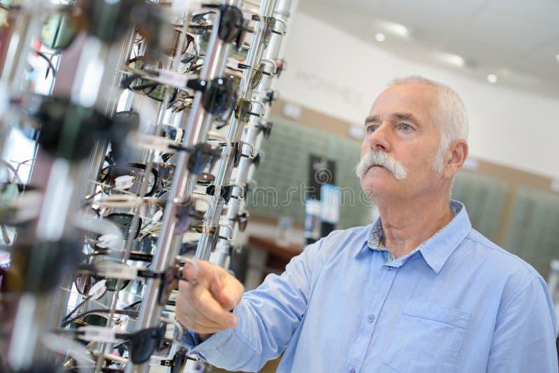 Starszego mężczyzna coosing okulary przeciwsłoneczni w sklepie obrazy royalty free